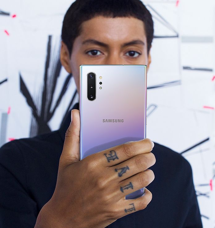 Man holding and looking at his Galaxy Note10 plus as he uses Face Recognition to unlock his phone
