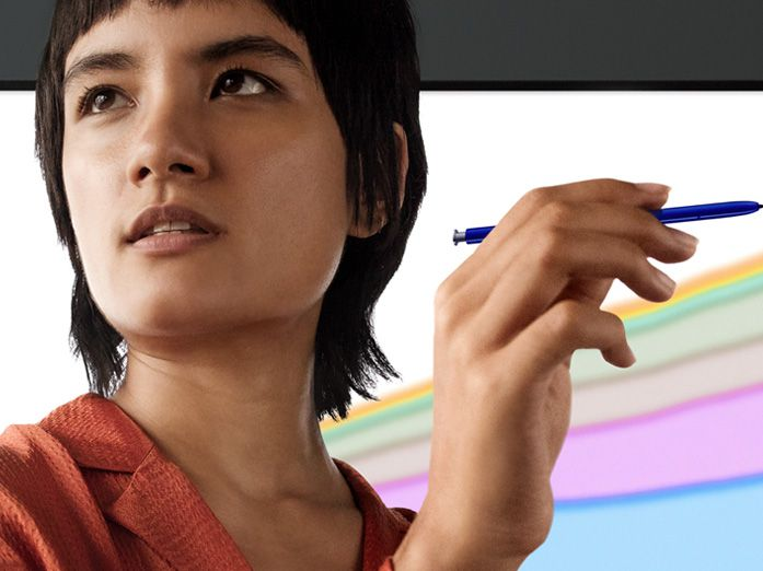 Woman standing in front of of a wall with an illustration on it holding S Pen