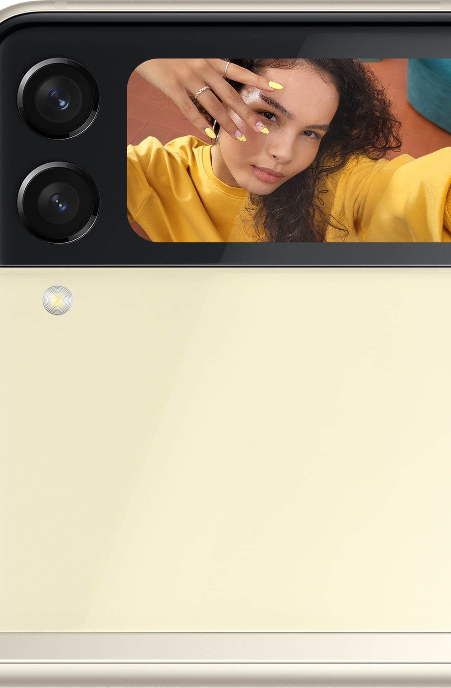 The Front Cover of Galaxy Z Flip3 5G with a woman taking a selfie shown in the Cover Screen.