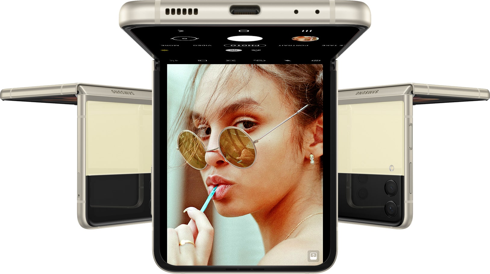 Three Galaxy Z Flip3 5G phones, all in Flex mode and upside down. The phone facing forward has the Camera app on the Main Screen, and a woman is staring into the camera.