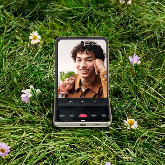 Galaxy Z Flip3 5G in Flex mode in the middle of a field with a video call on screen. The person on the other side of the call is a man holding a drink.