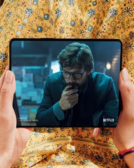 Hands holding Galaxy Z Fold3 5G, unfolded. The Main Screen displays a scene from a Netflix video of a man holding his hand up to his face.