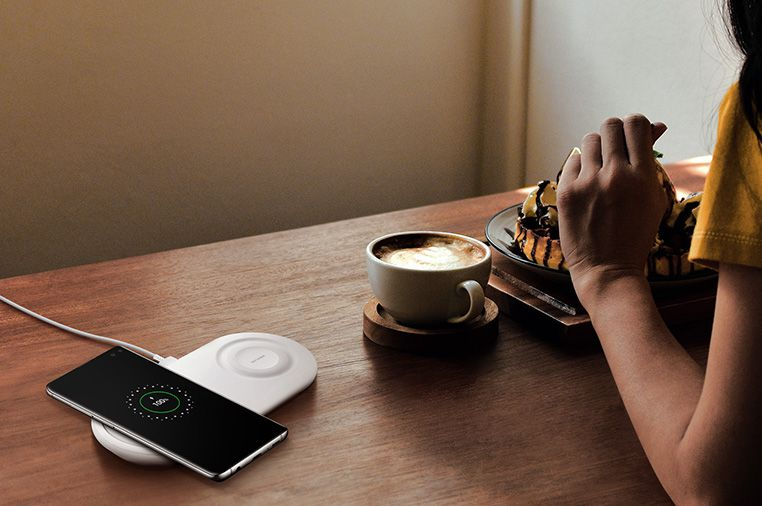 Image of a person sitting at a table with a coffee cup, eating with their Galaxy S10 plus charging on the Wireless Charger Duo Pad.