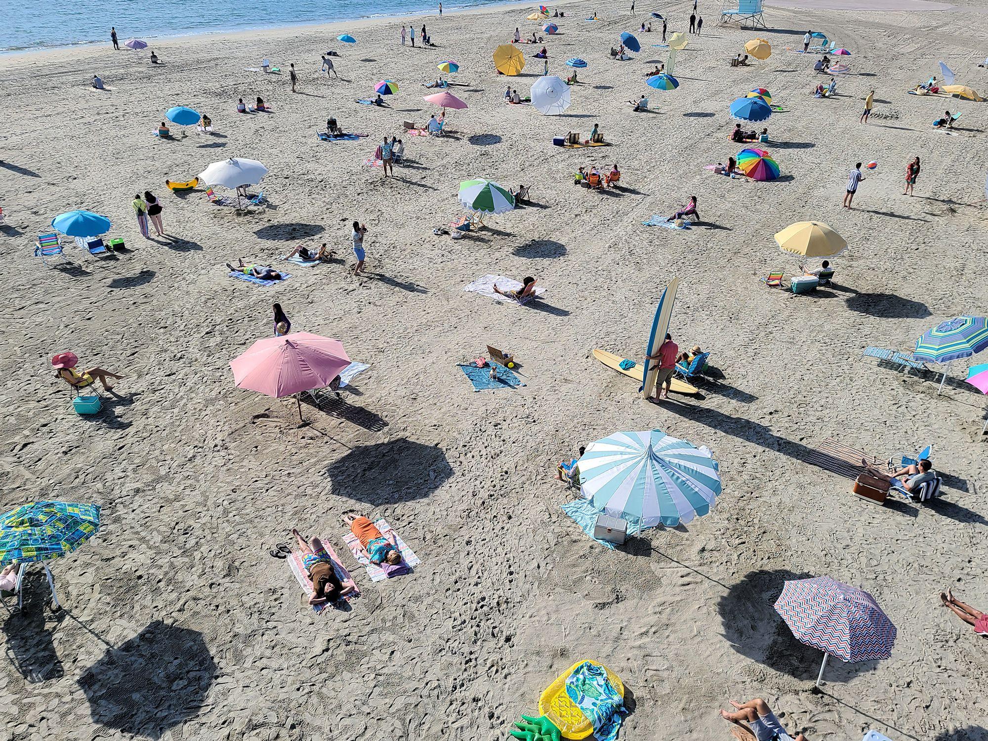 Фотоснимок людей на пляже, сделанный камерой телефона Galaxy S20 Ultra 5G. При увеличении изображения мы видим смешную сцену с собакой, сидящей на полотенце в розовых очках. Это иллюстрирует возможности функции Space Zoom для фиксации моментов, которые мы бы просто не заметили при съемке обычной камерой