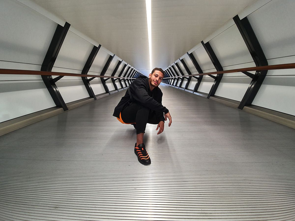 Photo captured by the Ultra Wide Camera of a man squatting in the middle of a long hallway