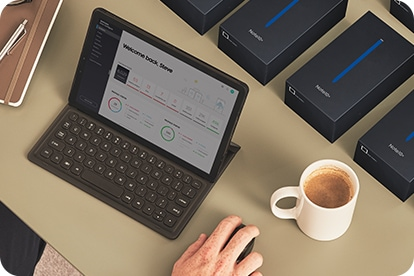 A desktop scene with someone working on their Galaxy Tab S5e with the Knox Configure GUI onscreen. Behind the Tab S5e is a row of Galaxy Note10+ boxes, ready to be configured.