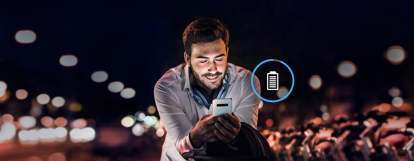 Image of man working at night on Galaxy S10 plus with overlaid battery icon.