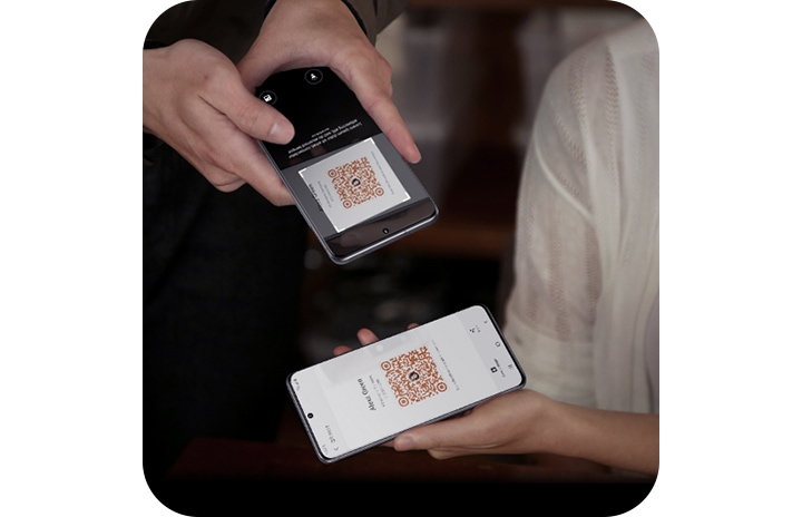 Two people, each holding a Galaxy S20 Ultra. One person is holding the phone with a QR Code on screen, and another is using her phone to scan the QR code