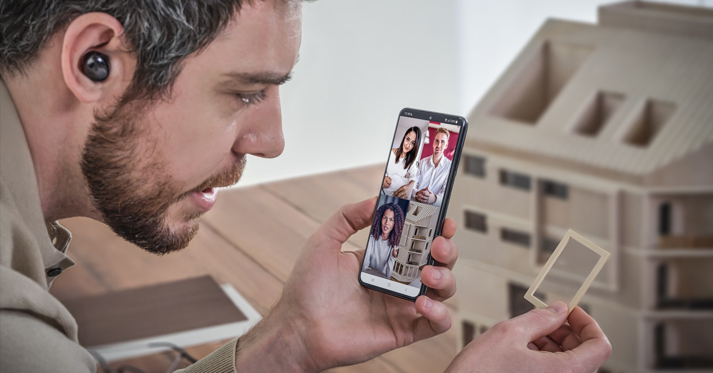 Man holding Galaxy S21 Ultra 5G displaying a video conference call with three people as his screen shows the rear camera view, demonstrating how easy it is to communciate and work together remotely.