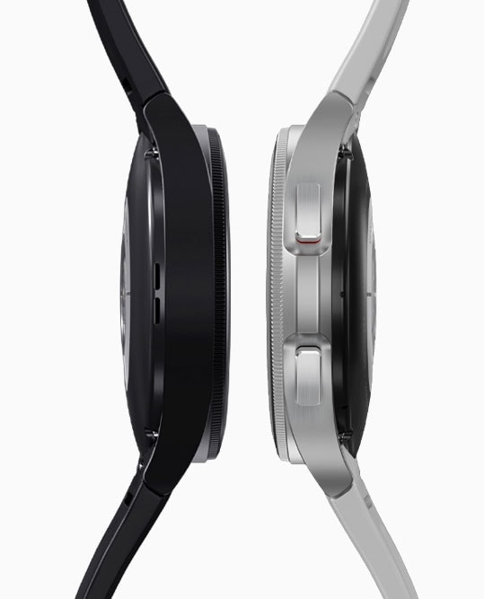 Two Galaxy Watch4 Classic devices, black on the left and silver on the right, are placed next to each other in a sideways view.