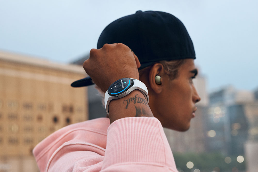 A man with a snapback on backwards is wearing Galaxy Buds2 and a Galaxy Watch4 Classic device. He is holding his right arm up, where he is wearing the watch, and is looking far away in a cityscape.