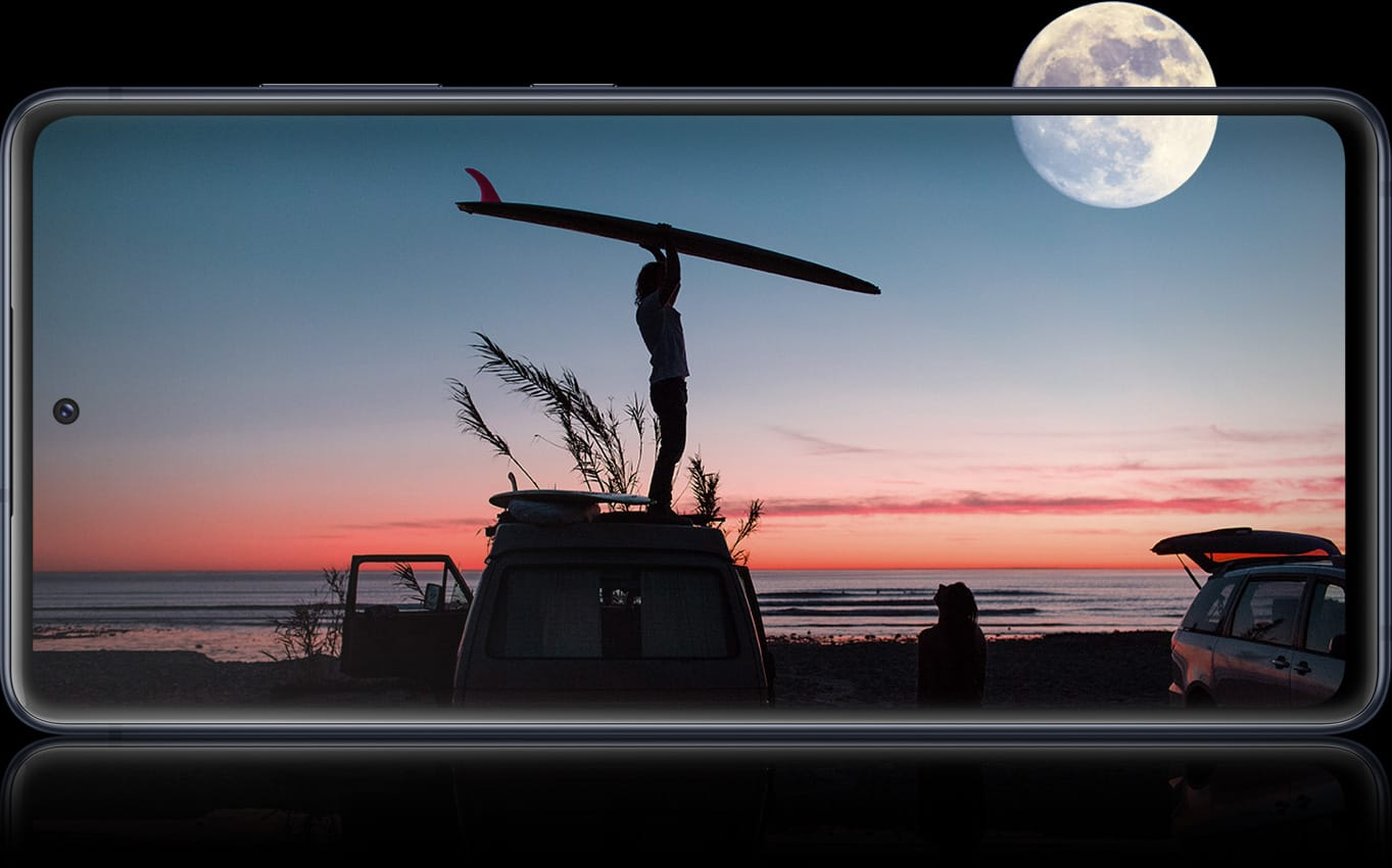 Galaxy S20 FE with a nighttime photo onscreen showing a shadow of a person holding a surfboard above their head. Above is a full moon in the sky. The full moon is half outside of the screen, representing the all-day battery life available on Galaxy S20 FE.