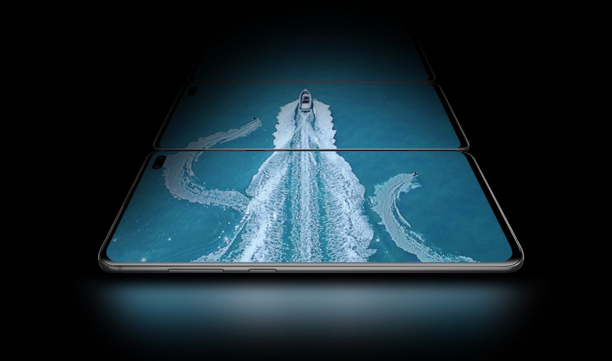 Three Galaxy S10 plus phones in landscape mode, laying flat above the one in front of it, seen at a slight angle from the Bixby and volume button side. On the three screens there is an aerial shot of a boat in water with two water skiers, showing the expansiveness of the Infinity-O Display.
