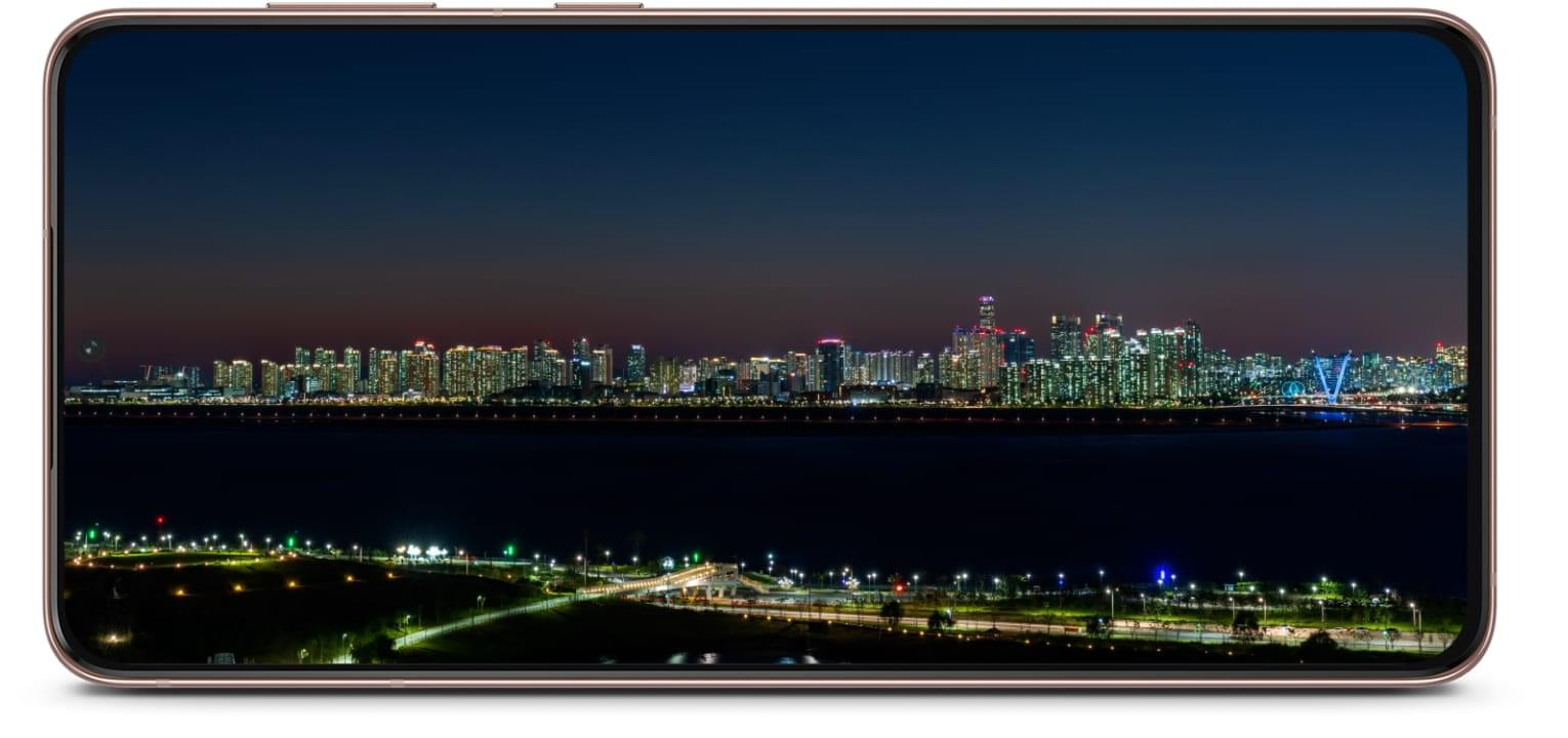 Galaxy S21 Plus 5G phone seen from the front in landscape view with a cityscape onscreen. The cityscape lighting goes from day to night to demonstrate using the phone from morning until night.