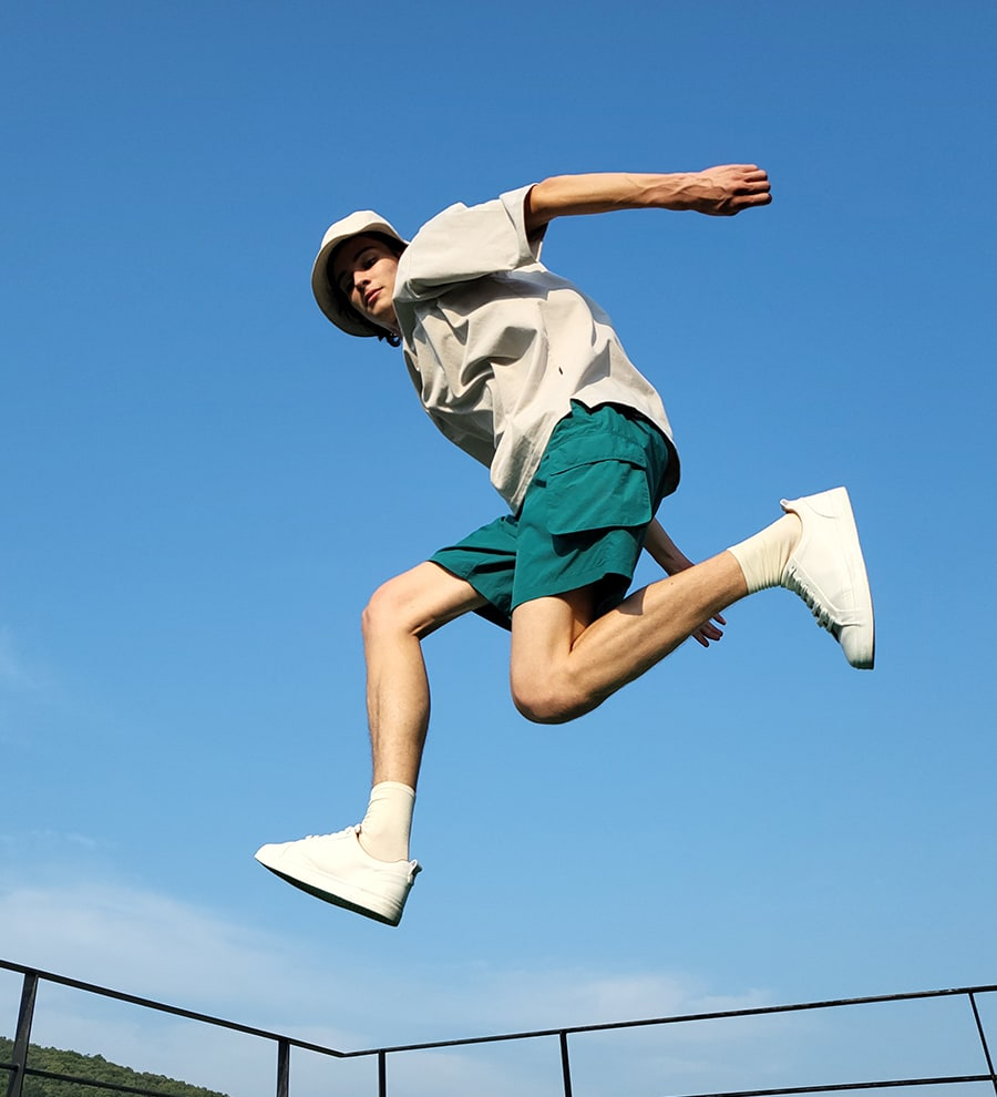 A man jumping and looking down into the camera.